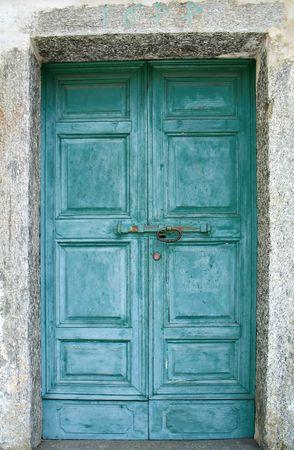 door bolt: Un viejo verde puerta de una iglesia en un pueblo de monta�a, Italia