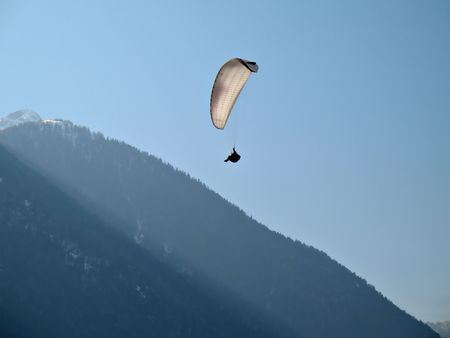 paraglide: A paraglider is flying in the blue sky near a mountain with his paraglide