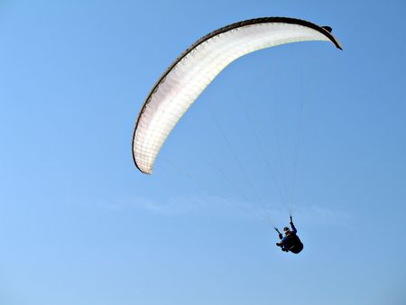 winter escape: A paraglider is flying in the blue sky with his white paraglide Stock Photo