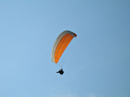 paraglide: A paraglider il flying in the blue sky with his colourful paraglide