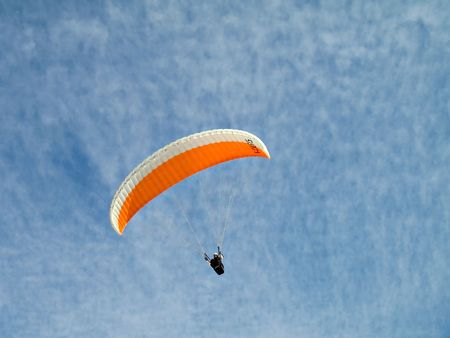parapendio: A paraglider il flying in the sky with his colourful paraglide