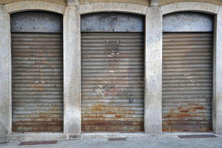 verlaagd luiken van een verlaten shop, rolling rusty, vuil en mislukking cityscape
