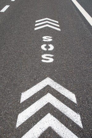 emergency lane: SOS sign with direction arrows on an emergency lane of a freeway Stock Photo