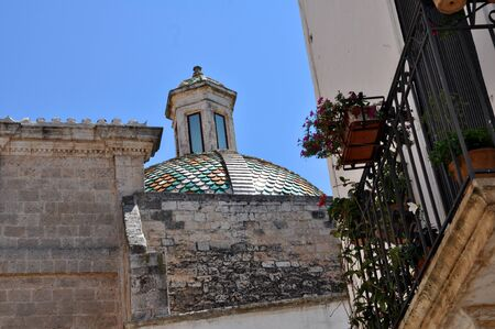 Ostuni lane in the Old Town (the White City) with a dome in the background, Puglia, Italy