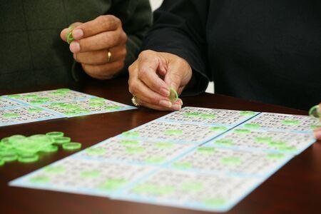 bingo: La gente que juega al bingo con fichas y tarjetas Foto de archivo
