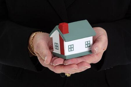 downsizing: Senior woman holding a small house in her hands Stock Photo