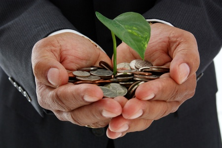 Hispanic man holding a plant in a pile of money photo