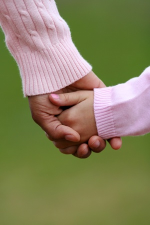 holding hands while walking: Mother and daughter holding hands while walking together Stock Photo