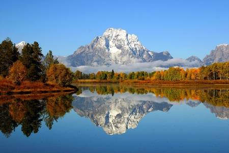 Reflection of mountain range in a lake at Grand Teton National Park photo