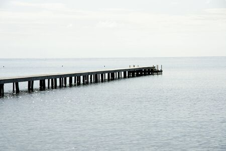traquil scene: Dock extending into the ocean Stock Photo