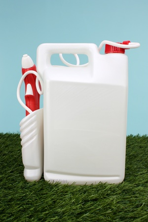 White And Red Spray Container In The Grass Banco de Imagens