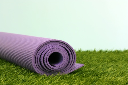 Purple Yoga Exercise Mat On Green Grass photo