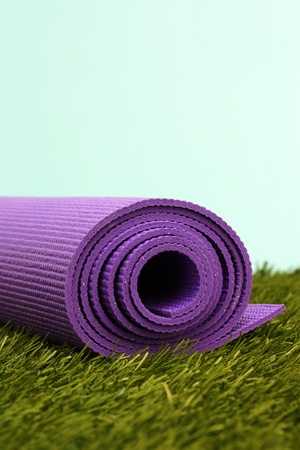 Purple Yoga Exercise Mat On Green Grass Stock Photo