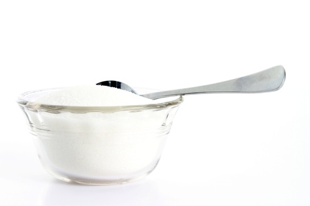 Granulated sugar on white background with teaspoon