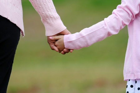 Mother and daughter holding hands while walking together Archivio Fotografico