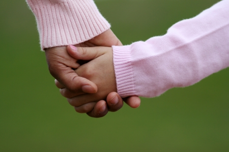 mother and child: Mother and daughter holding hands while walking together Stock Photo
