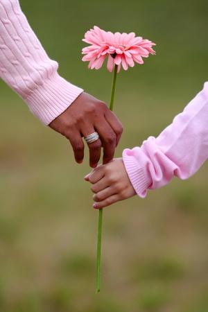 mother with daughter: Madre e hija, sosteniendo una flor, mientras que caminando juntos Foto de archivo