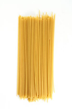 raw: Uncooked spaghetti laying on a white background