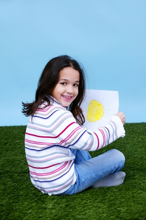 Young girl sitting in the grass holding a picture of the sun Stock Photo - 13139397