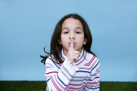 Girl giving the quiet sign with her finger and mouth Stock Photo - 13147439