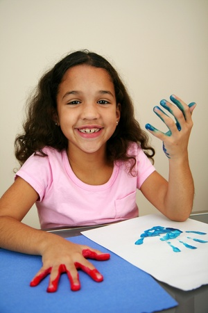 Girl at school finger painting photo