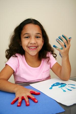 child finger: Girl at school finger painting