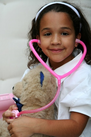 Young girl plays doctor or nurse with stuffed animal Stock Photo - 13141959