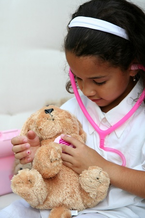 Young girl plays doctor or nurse with stuffed animal Stock Photo