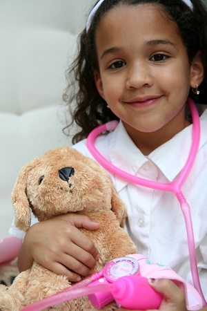 Young girl plays doctor or nurse with stuffed animal Stock Photo - 13139459