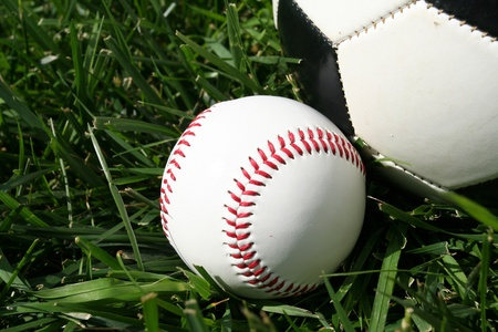 Baseball and soccerball sitting on a field photo