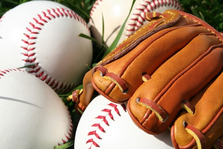 little league: A baseball glove surrounded by balls on a field