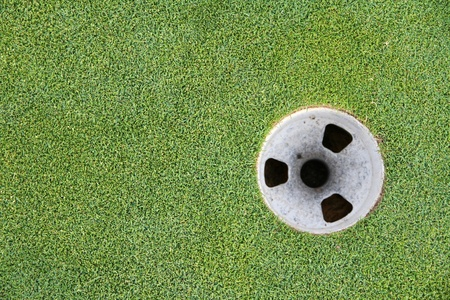 Golf cup with green grass surrounding it photo