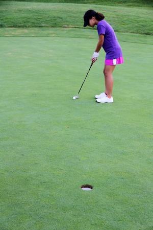 teen golf: Chica poner la pelota en un campo de golf Foto de archivo