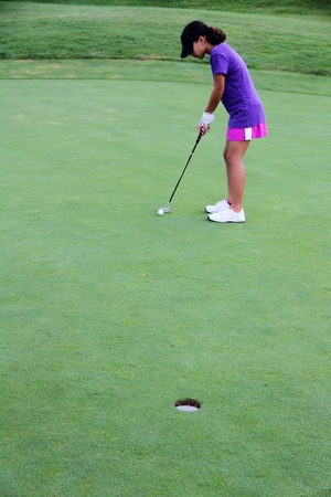 Girl putting ball on a golf course photo
