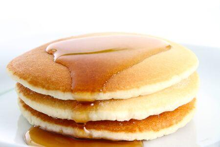 白い背景の上にシロップをパンケーキのショート スタック 写真素材