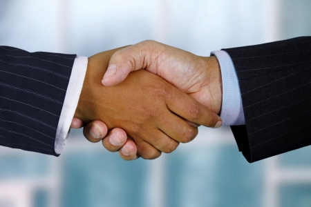 Business team shaking hands while in their office Stock Photo