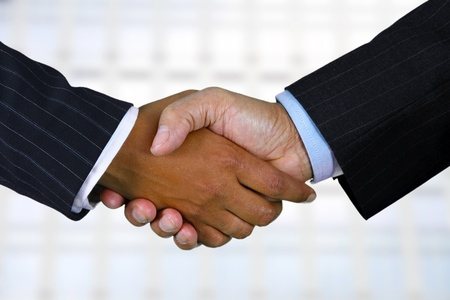 Business team shaking hands while in their office Zdjęcie Seryjne