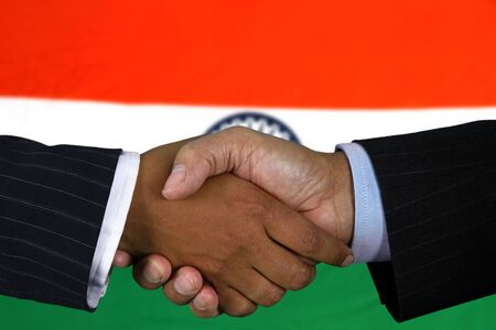 foreign trade: Business team shaking hands in front of the flag