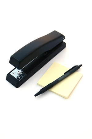 Stapler post it notes and a pen sitting on a white background