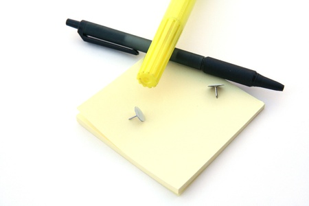 Post it notes and a pen sitting on a white background