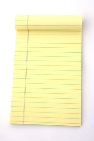 Yellow legal pad of paper set against a white background Imagens