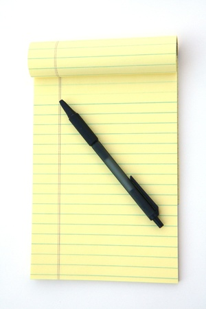 note pad and pen: Yellow legal pad of paper set against a white background Stock Photo