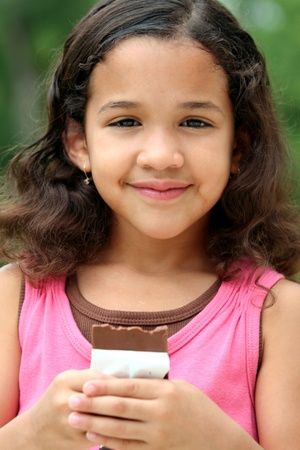 Young girl outside eating a candybar photo