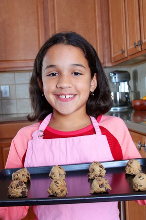 Girl baking chocolate chip cookies in the kitchen photo
