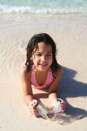 Young girl playing in the sand at the beach photo