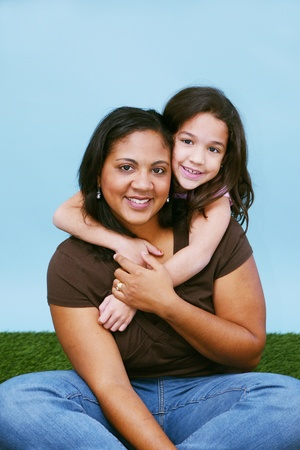 Young girl sitting in the grass with her mother Stock Photo - 13155092