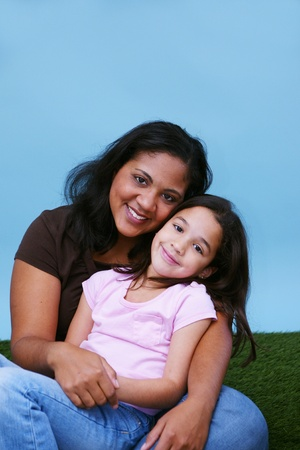 Young girl sitting in the grass with her mother Stock Photo - 13150075