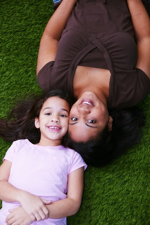 interracial love: Young girl sitting in the grass with her mother Stock Photo