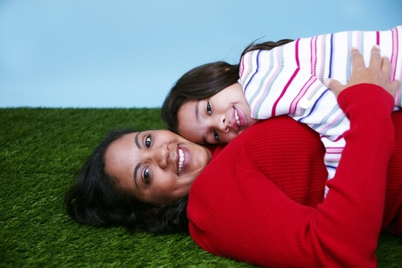 Young girl sitting in the grass with her mother photo