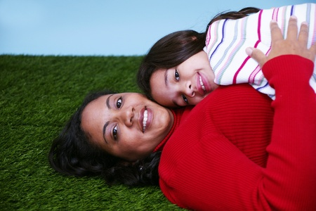 Young girl sitting in the grass with her mother Stock Photo - 13155090